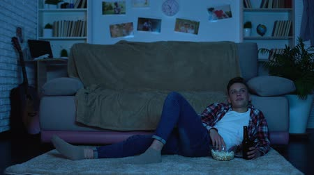 szülői : Teenage boy drinking beer and eating snacks watching movie, alcohol addiction
