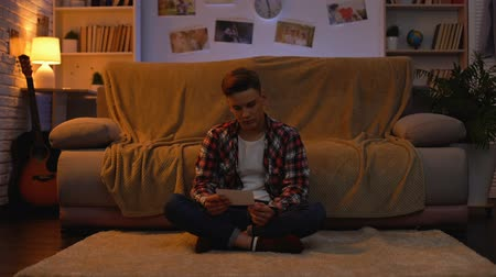 misunderstood : Sad lonely student looking at girlfriends photo, suffering breakup, relations Stock Footage