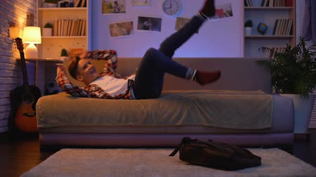 coming home : Satisfied smiling teenager student coming home, lying down on sofa, first job