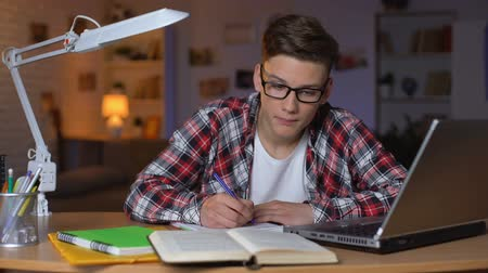 reference : Young boy writing summary preparing for test making project in college education