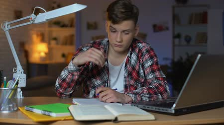 fegyelem : Left-handed overloaded teenage student preparing for examination, feeling sleepy