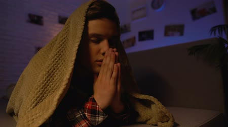 культ : Religious teenager praying covered with blanket, belief in god, sectarianism