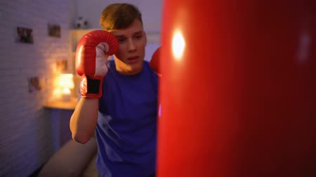 napětí : Teenager in gloves punching boxing bag, dreaming to become boxer, fitness Dostupné videozáznamy