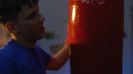 napětí : Exhausted teenager hugging punching bag after intensive workout, fitness, sport