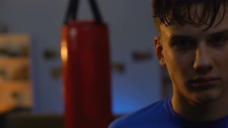 на камеру : Sweaty teenager looks seriously after intensive boxing workout, facing challenge Стоковые видеозаписи