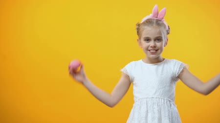 headband : Happy Easter greetings, smiling little girl holding colored eggs in front eyes
