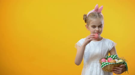 saç bantı : Happy Easter text, adorable schoolgirl taking pink egg from basket greeting card Stok Video