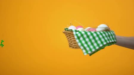 boiled egg : Happy Easter inscription and basket with colored eggs on yellow background, fest