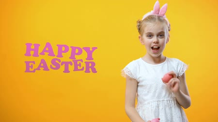 saç bantı : Happy Easter sign, excited little girl playing and dancing with colored eggs Stok Video