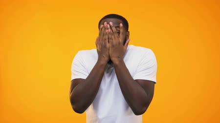 etnia africano : Surprised afro american guy peeping through fingers against yellow background