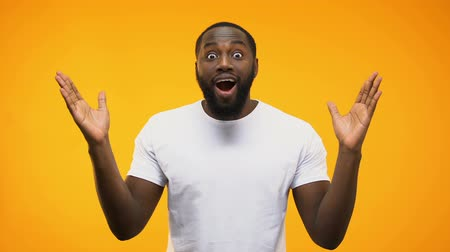 dark skinned : African american man is amazed, throwing up arms, isolated on yellow background Stock Footage