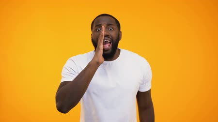 africký : Young afro american man is calling for you loudly, isolated on yellow background