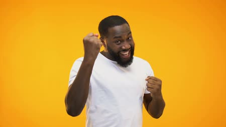 piyango : Young black guy making success gesture with hands, isolated on yellow background