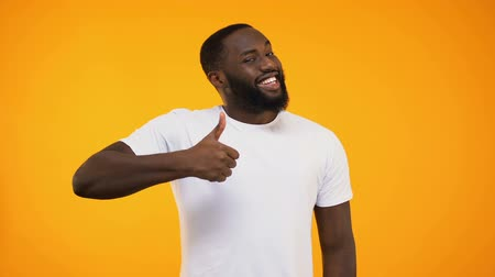 отношение : Young bearded black guy giving thumbs up, smiling at camera on yellow background Стоковые видеозаписи