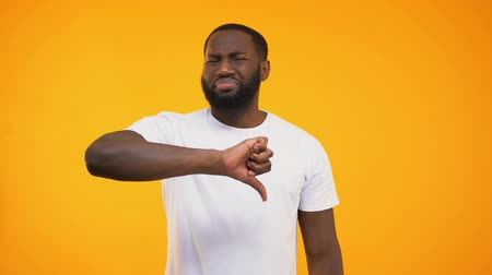 errado : Disappointed afro american guy showing thumbs down isolated on yellow background Stock Footage