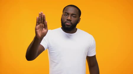 alt : Young black guy showing stop gesture with palm, isolated on yellow background