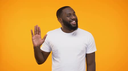 tebliğ : Affable young black man waving hand neighborly, isolated on yellow background