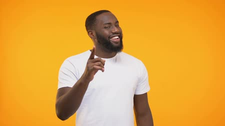 gösteren : Smug afro-american man pointing his finger knowingly against yellow background