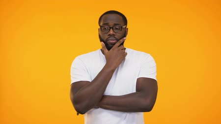 мысль : Smart young black student in glasses thinking about answer, yellow background