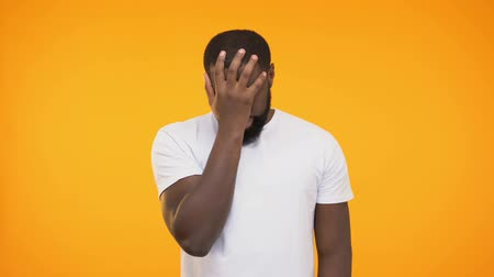 shame : Disappointed afro american male doing facepalm gesture against yellow background Stock Footage