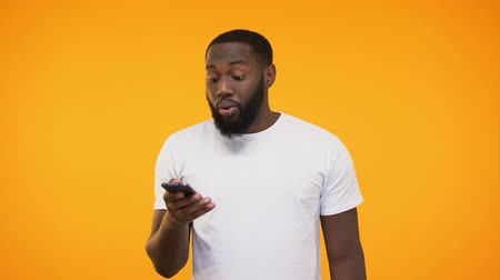 approving : Young african american man holding cellphone, job approving message, application Stock Footage