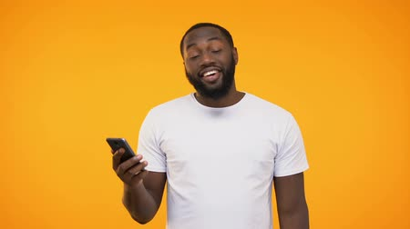 rekomendacja : Black man is satisfied, looking at phone, giving thumbs up on camera, new app Wideo