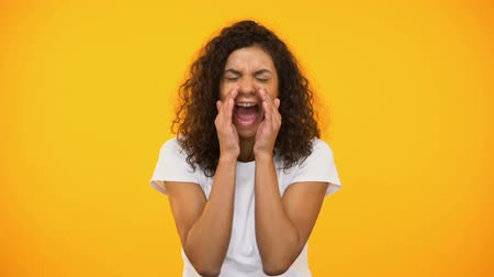 zařvat : African american girl screaming to camera against yellow background, protest
