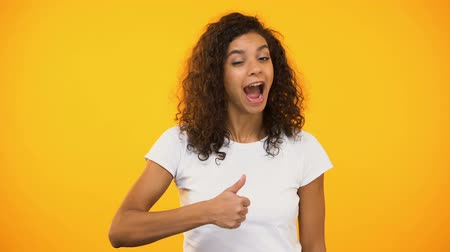 impressão tipográfica : Happy mixed-race lady showing thumbs-up and winking on camera, positive feedback