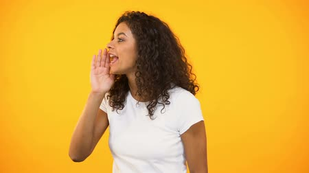 holler : Biracial woman announcing shop discounts, calling for friend, yellow background