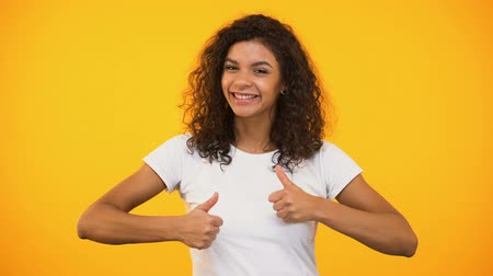 impressão tipográfica : Cheerful biracial woman showing thumbs-up and smiling against yellow background Stock Footage