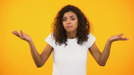 descuidado : Afro-american female shrugging shoulders, unsure of choice, yellow background Stock Footage