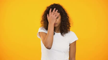 manichino : Discontent biracial lady gesturing facepalm on camera against yellow background