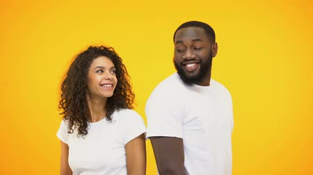 szétzúz : Beautiful multiracial couple flirting and smiling, isolated on yellow background
