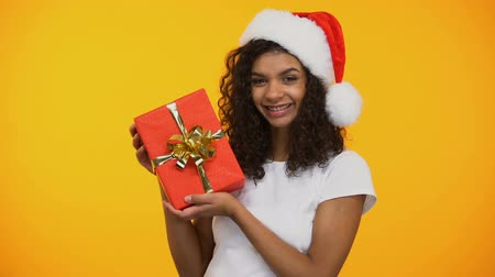 скидка : Cheerful mixed-race woman in santa claus hat holding red giftbox and smiling Стоковые видеозаписи