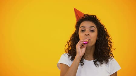 życzenia : Extremely happy woman blowing party horn and laughing, celebrating birthday