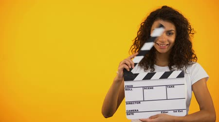 sinematografi : Beautiful mixed-race woman winking and holding clapper board, movie shooting