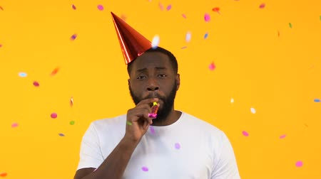 место : Upset Afro-American man in party hat whistling in horn under falling confetti