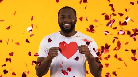 многонациональная : Afro-American man holding paper heart under falling confetti, romantic surprise