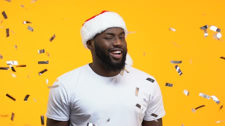 pozdrav : Black man in santa hat winking and showing thumbs up under falling confetti Dostupné videozáznamy