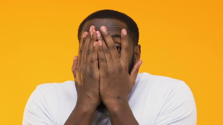 údiv : Shocked Afro-American man peeping through fingers against yellow background Dostupné videozáznamy