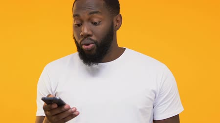 感動 : Impressed Afro-American man showing smartphone, using modern gadget, close-up 動画素材