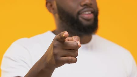 indicating : Smiling black man pointing finger into camera isolated on yellow background