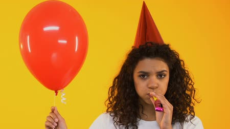 рог : Sad teenage girl blowing party horn, bored on birthday celebration, loneliness