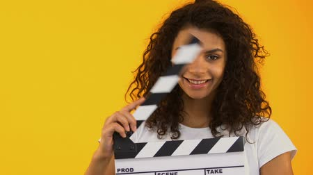 filmregisseur : Woman winking and using clapper board, shooting positive film, movie production