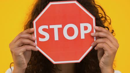 anti war : Biracial girl holding stop sign, protesting bullying or racism, gun violence Stock Footage