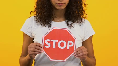 proibir : Young woman showing stop sign on yellow background, problem warning, restriction