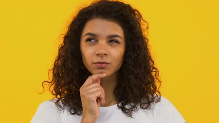 doubt : Pensive african woman on bright background thinking of choice, dreaming person