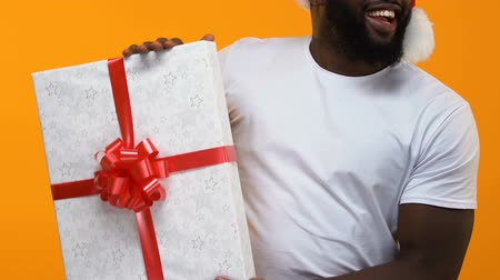 nagy : African young man white t-shirt holding big gift box, christmas sale, festivity