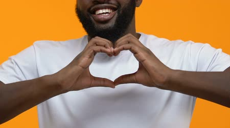 behulpzaam : Happy black man in white t-shirt showing heart sign hands, charity gesture, love Stockvideo
