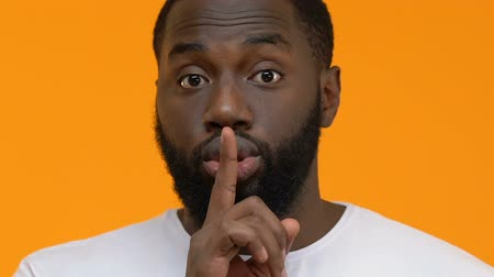 запрещено : Afro-american guy making silence gesture closeup, asking be quiet, conspiracy
